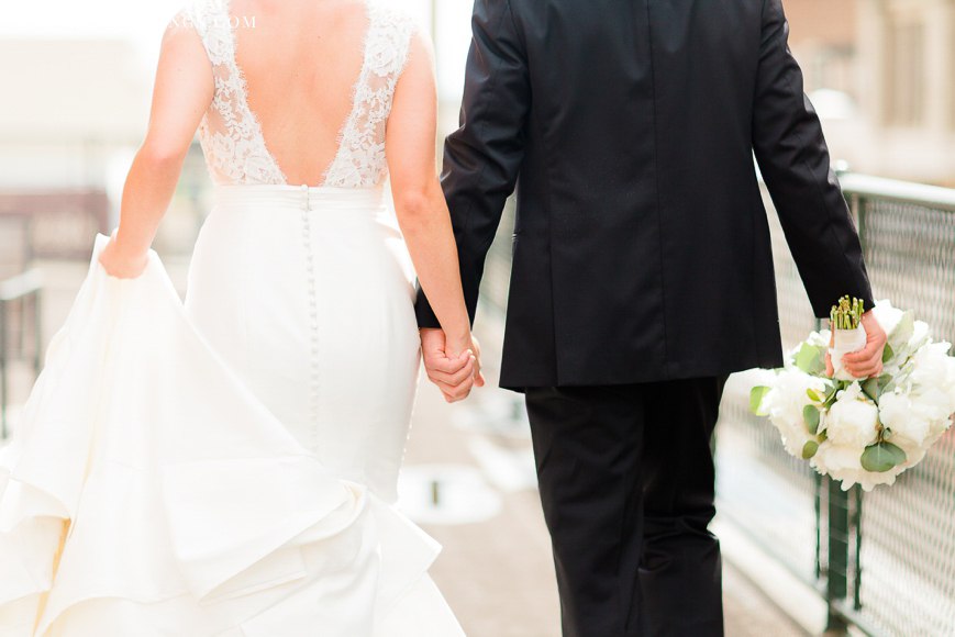 detail of bride and groom holding hands and walking away