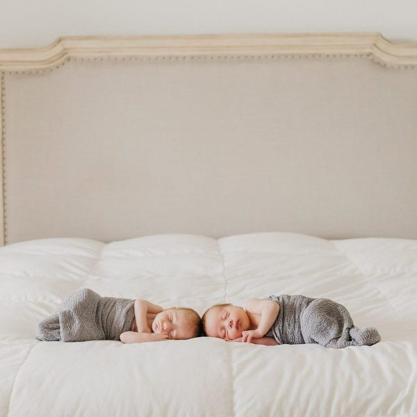 Two newborn babies sleeping on a bed