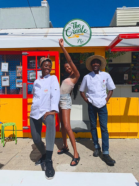 Pesy, Jide and a customer striking a pose outside of the brightly painted Beach 96th street location.