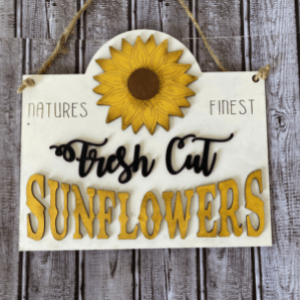 Wooden sign with wood cutout painted pieces, of the words Fresh cut sunflowers and natures finest and a sunflower in the middle