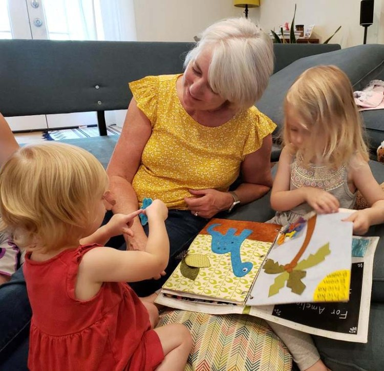 Sharing her busy book with little sister.   Busy Book made by Julie Cefalu @ The Crafty Quilter