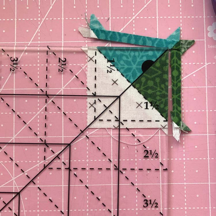 Using the Tucker Trimmer I to trim a half quarter square triangle @ The Crafty Quilter
