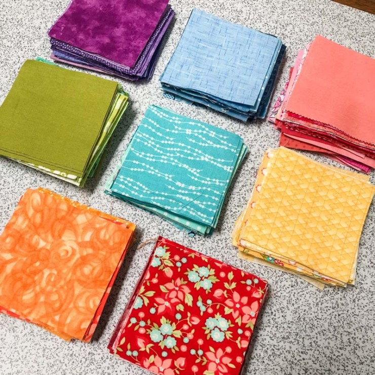 A rainbow of fabric squares are cut and ready for some Sampler Spree quilt blocks @ The Crafty Quilter.