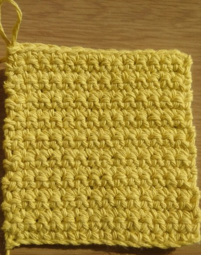 square crochet coaster in yellow recycled cotton yarn