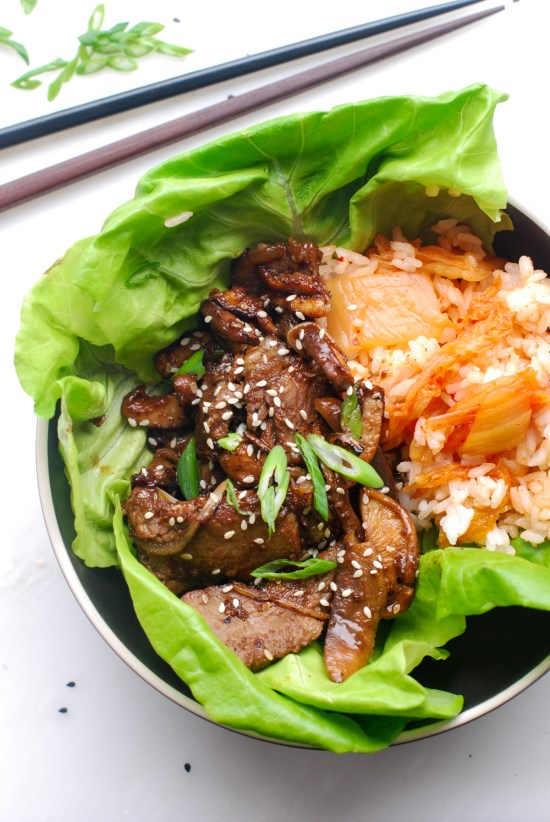 Overhead view of Korean BBQ rib eye steak in a bowl of lettuce leaves with kimchi rice.