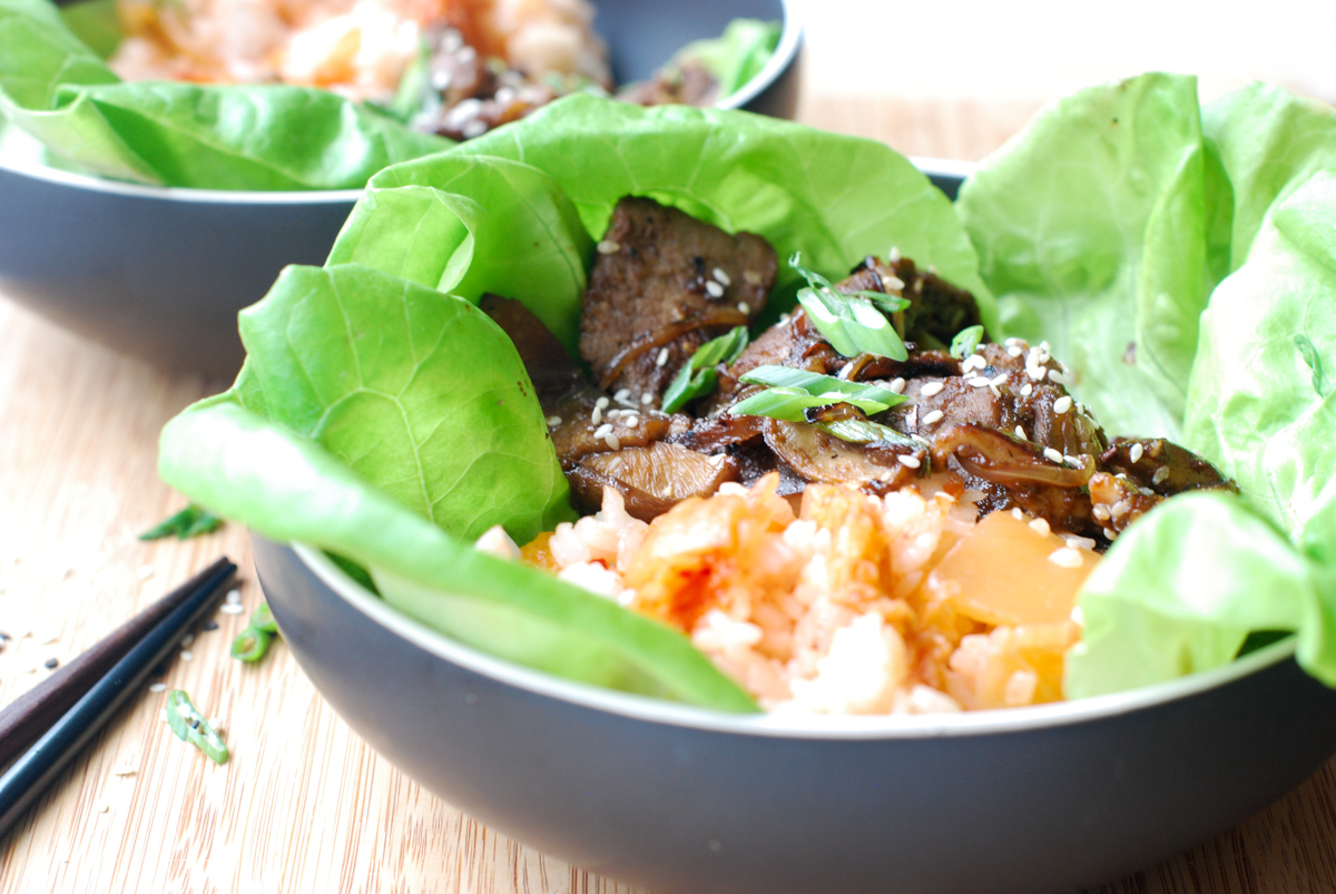 Side view of Korean BBQ rib eye steak in a bowl of lettuce leaves with kimchi rice.