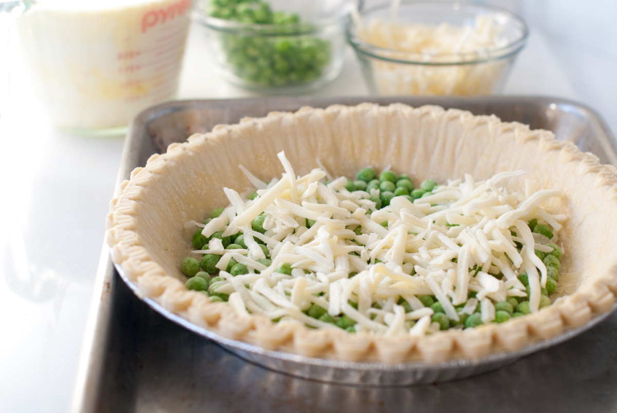 Quiche shell filled part way with cheese and peas, with egg mixture in the background.