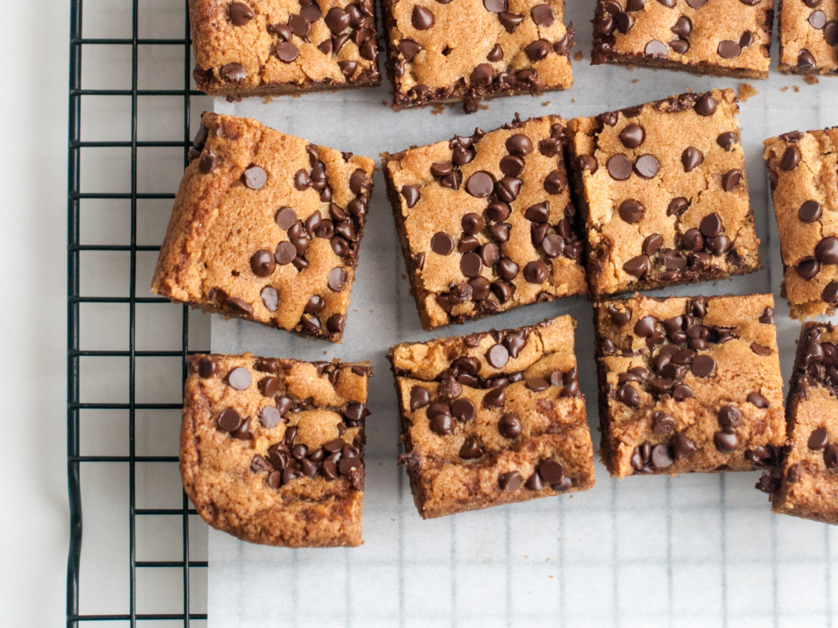 Overhead view of a batch of cut up blondie squares with melted chocolate chips on top.