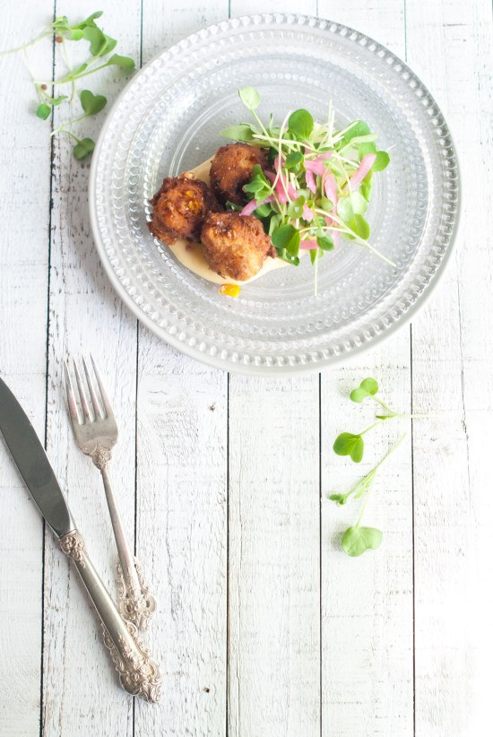 Overhead shot of a beaded plate with pepper jack cheese fondue topped with three corn and beer fritters along with baby radish greens and pickled red onions