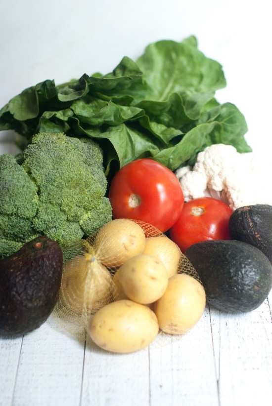 An assortment of fresh produce including tomatoes, cauliflower, avocado, potatoes, broccoli and Romaine lettuce.