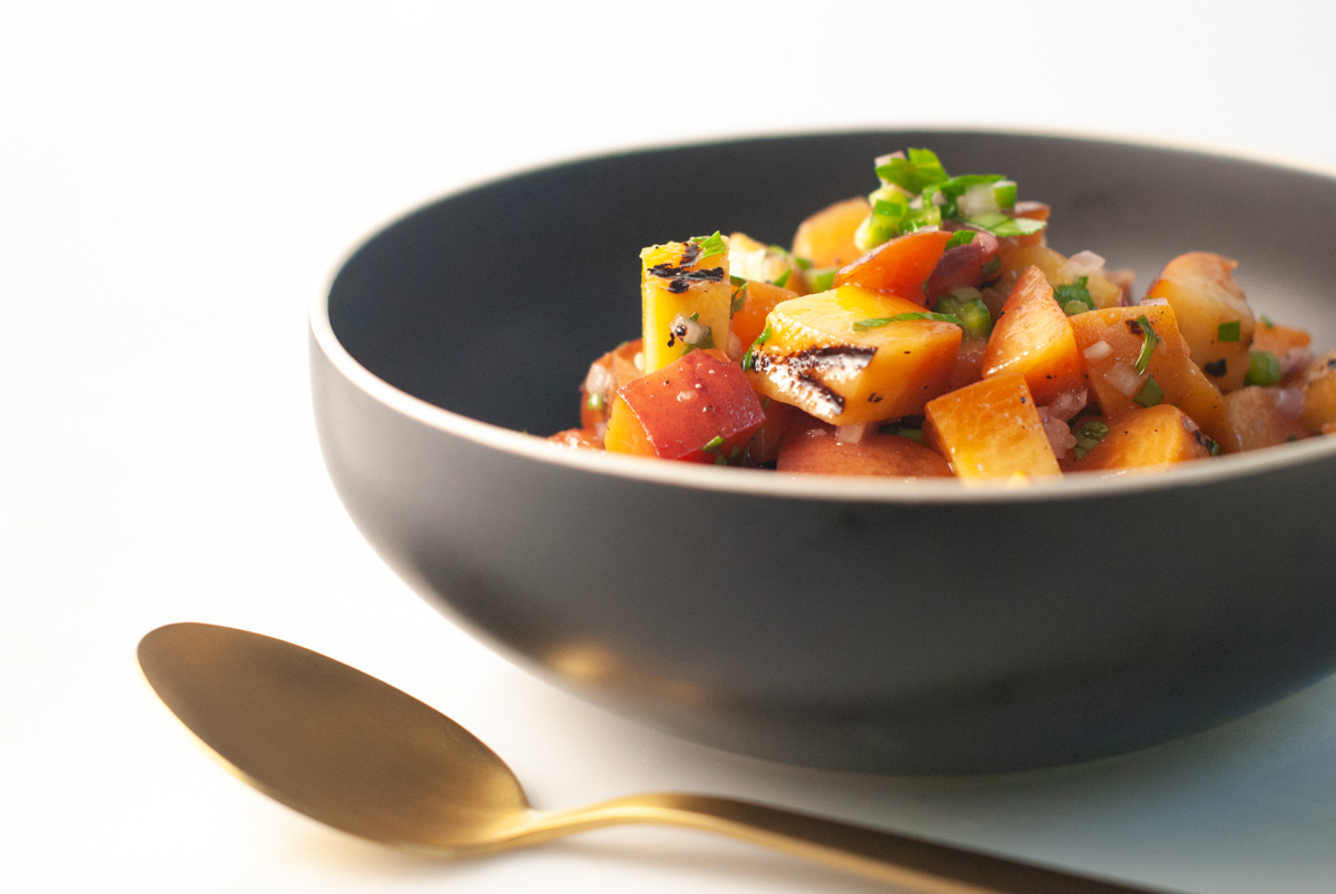 Black bowl filled with diced grilled peaches and jalapeno, with a gold spoon.