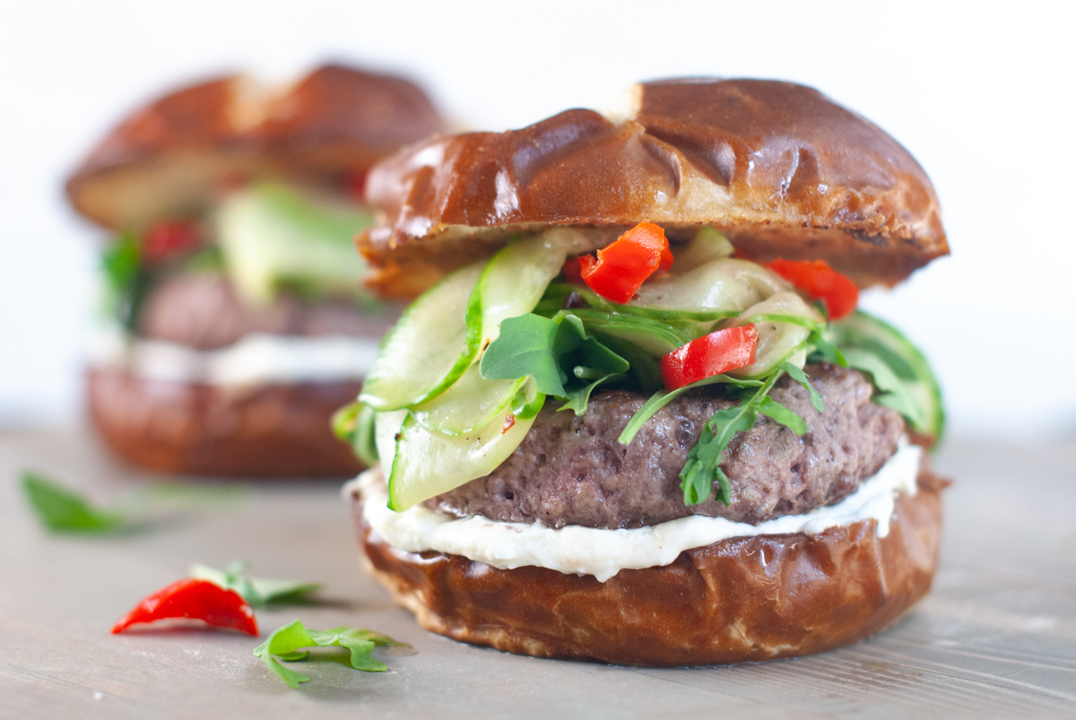 Side view of a seared lamb burger topped with layers of spicy cucumber and cherry peppers, arugula and a goat cheese mayo.