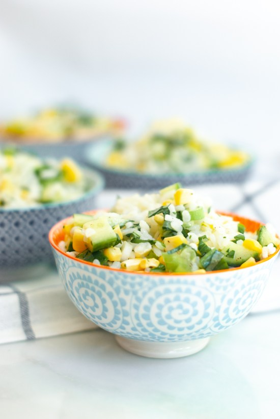 Four decorative bowls filled with risotto rice salad mixed with corn, cucumber, green onion and lots of fresh herbs.