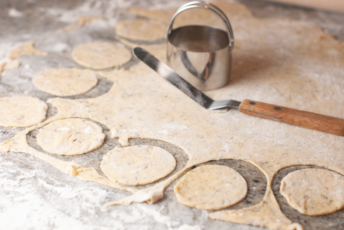 Round circles of dough cut out, ready to be baked into crackers.