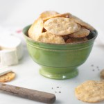 A green bowl overflowing with homemade crackers.