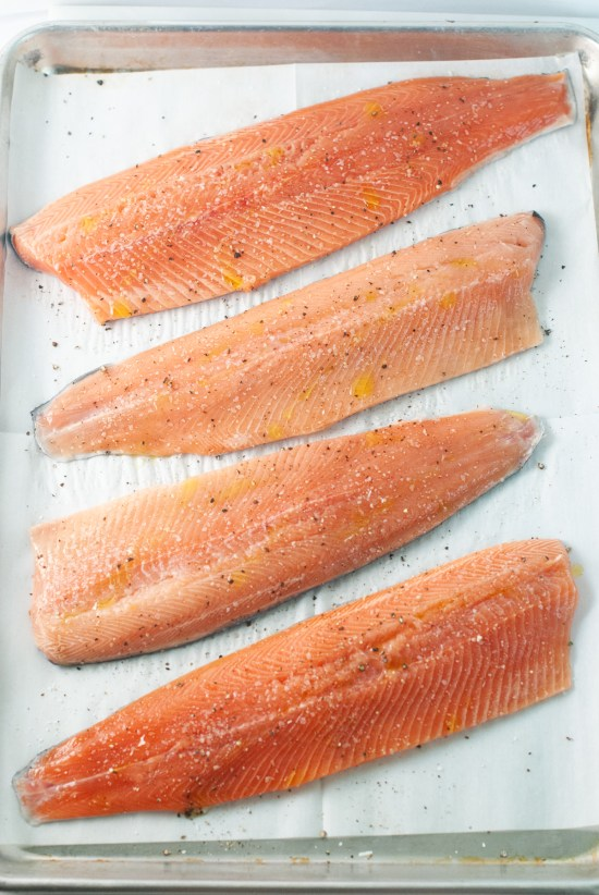 Four trout filets arranged on a sheet tray ready for baking.