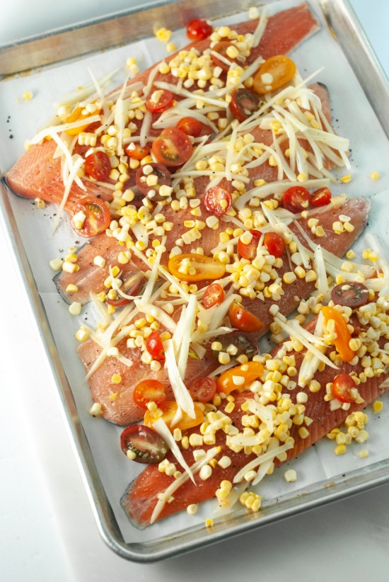 Trout filets topped with sliced fennel, cherry tomatoes and corn kernels ready to be baked in the oven.
