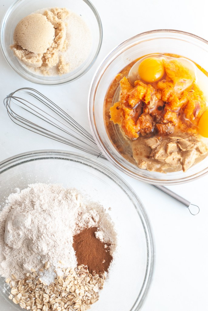 Three bowls or measured ingredients - one bowl with oats, flour, cinnamon, another bowl with mashed sweet potatoes, eggs, oil, almond butter and vanilla and a third bowl with white and brown sugars.