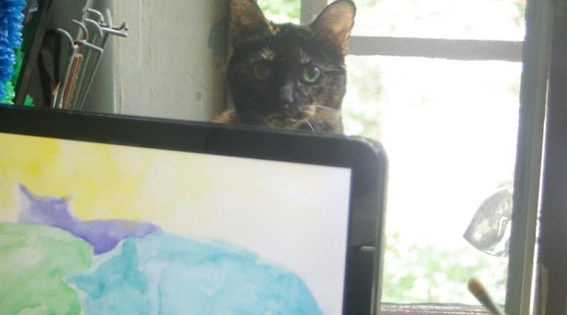 tortoiseshell cat behind computer monitor