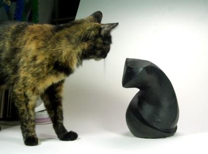 tortie cat with sculpture