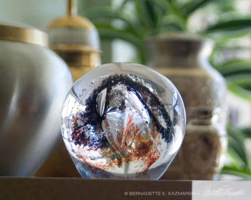Cremains incorporated into a handmade glass ball along with a variety of urns.