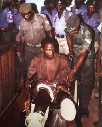Anini, on a wheelchair, leg amputated, after his capture