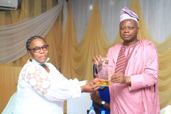 Rev. Mrs. Adenike St. John presenting the merit award to the honoree, Prof. Olayinka