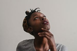 A young African-American woman looks upwards with a concerned look, touching her chin as if wondering about something. Image credit: Tachina Lee at unsplash.com