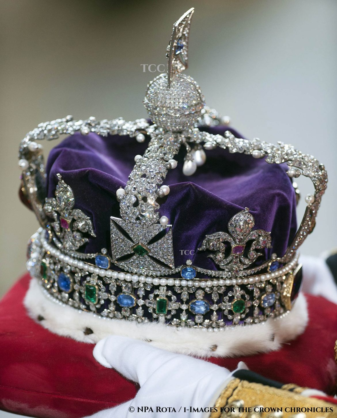 a close up view of the imperial state crown with a velvet purple cap, ermine trimmed band, with two arches that cross in the centre, formed in oak leaves and pearl acorns. fleur de lis and cross pattee shapes sit atop a friezework band of diamonds, studded with emeralds and sapphires