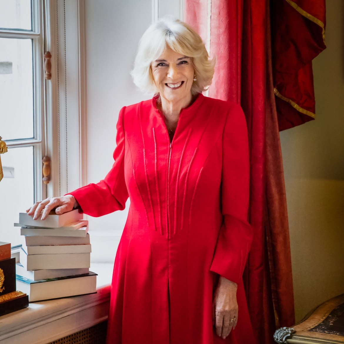 Camilla, The Duchess of Cornwall, in a red coat dress with her hand on a pile of books to launch her Reading Room