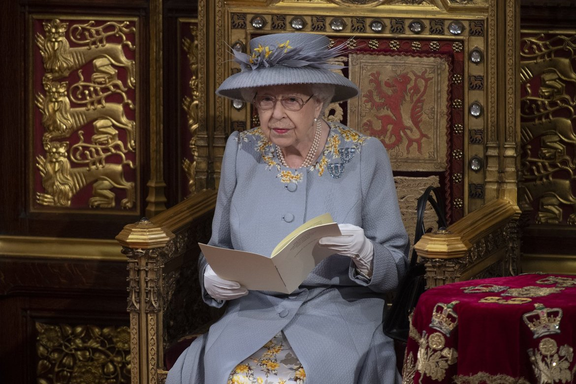 the queen, wearing a dove grey coat and hat with yellow flowers, reads from a booklet in the house of lords; she sits on a golden throne with heraldic emblems at the state opening of parliament