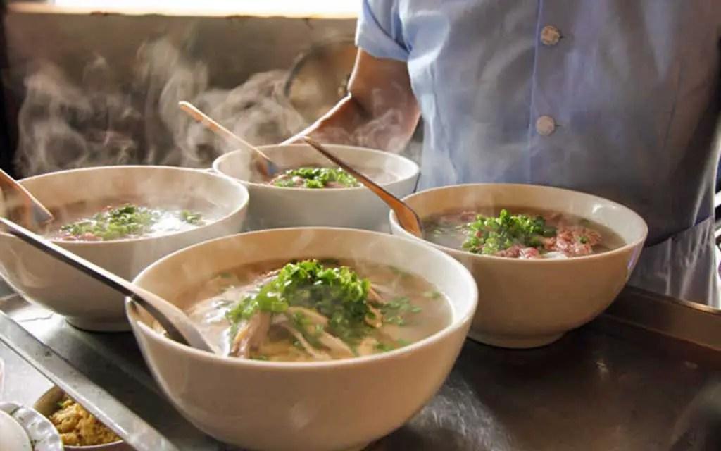 4 steaming bowls of Vietnamese Pho Bo, a popular street food in Hanoi