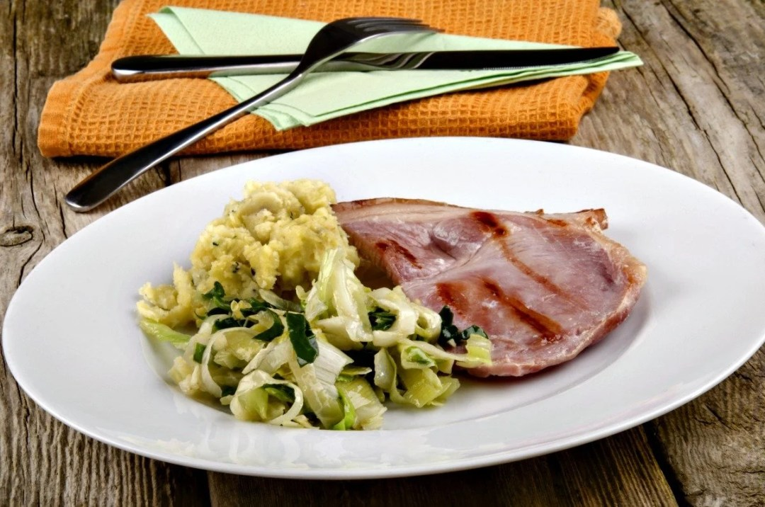 grilled bacon with cabbage and mashed potato on a plate