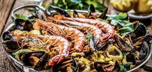 Traditional seafood paella in the pan on a wooden old table