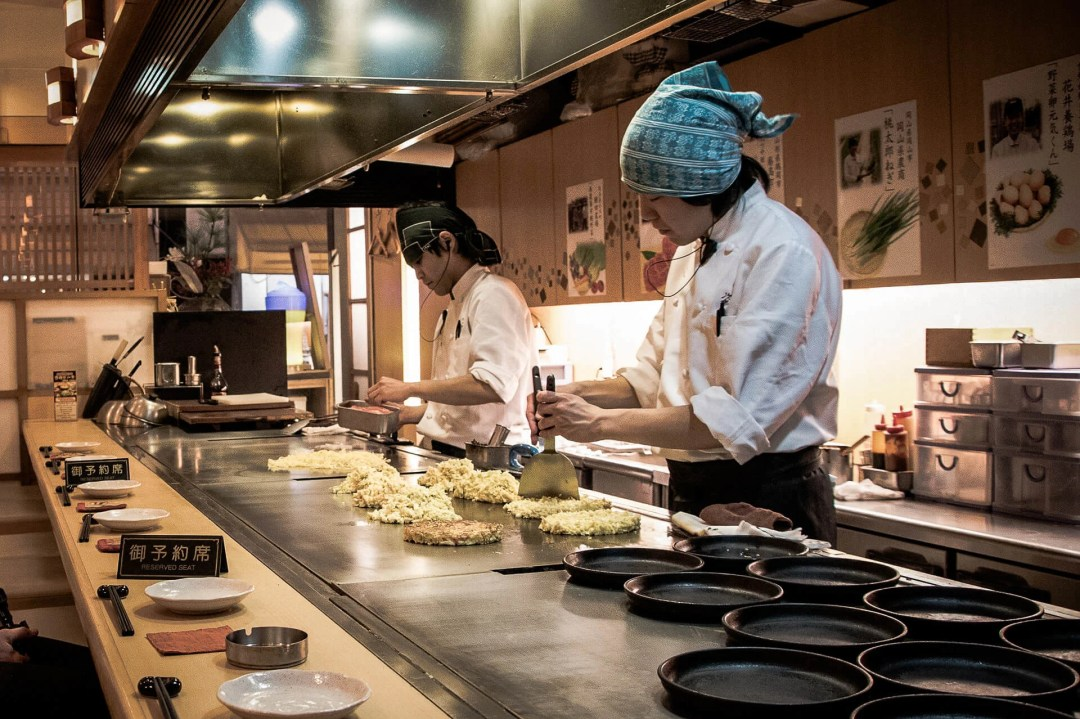 Two Japanese chefs in the kitchen making okonomiyaki