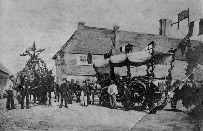 "Waggons decorated for the Harvest Home parade on September 14th 1864. The Order of Proceedings required men to have a bouquet of three ears of wheat on their left breast. The procession was headed by the oldest labourers and the ""musical band""."