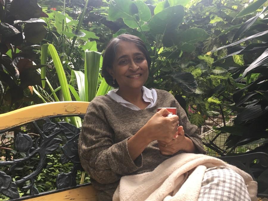 Poonam Bir Kasturi posing in her garden with a cup in her hand.