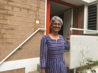 Chitra Vishwanath standing in front of her home dressed in a purple kurta.