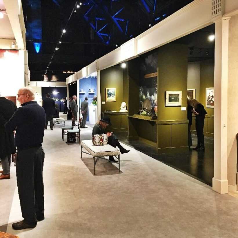 a row of booths at the Winter Antiques Show in the Park Avenue Armory