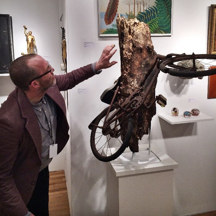 man touching a rusty bicycle encased in a tree stump at the Outsider Art Fair NYC