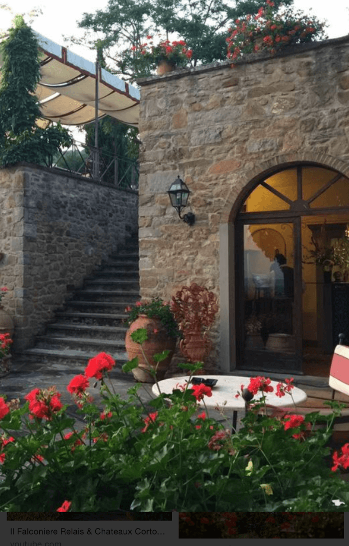 Stone Buildings at Il Falconiere with red and white flowers