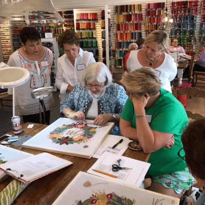 Patricia Sone teaching needlepoint stitches in a class