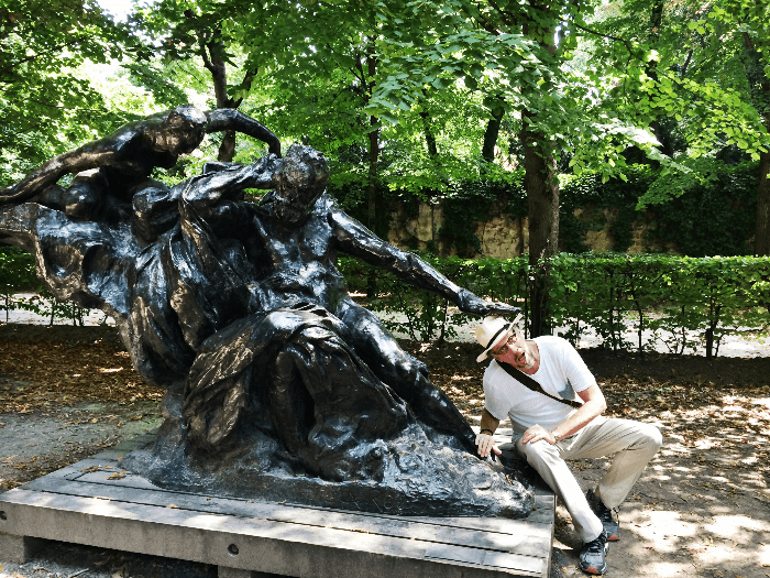 Will Evans in the Rodin Museum Garden under a bronze sculpture