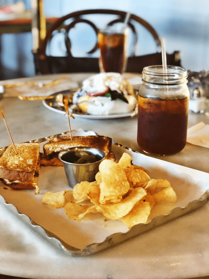 Metal Tray with a sandwich and potato chips with a glass of iced tea