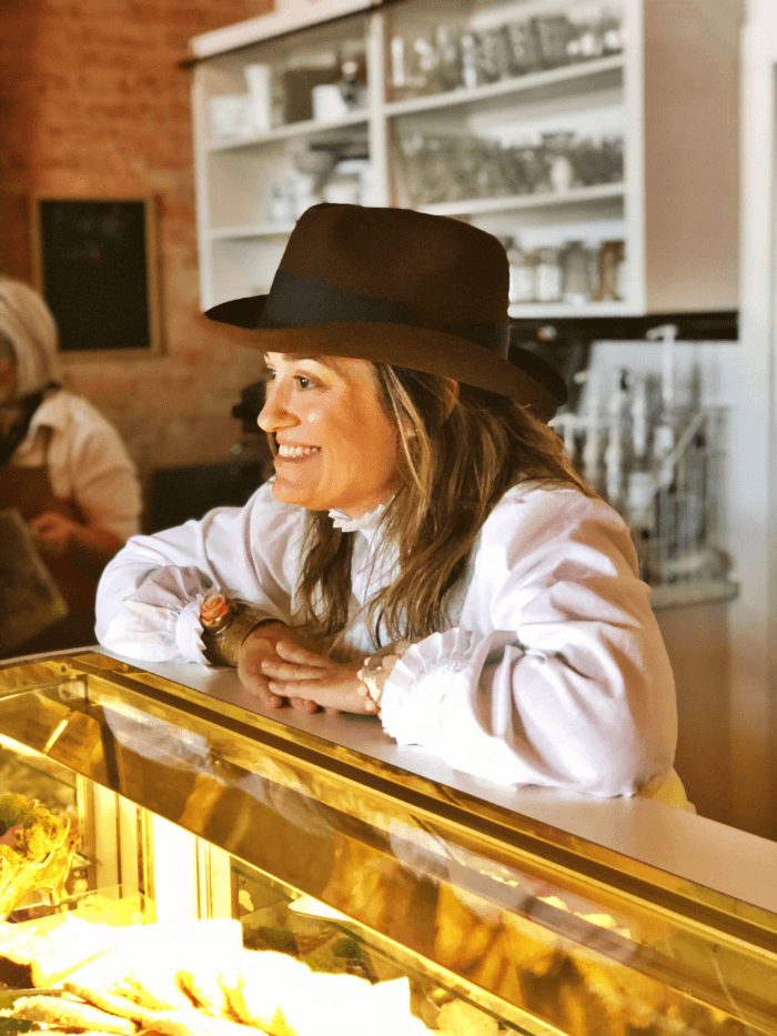 Woman in a black cowboy hat leaning on a glass counter