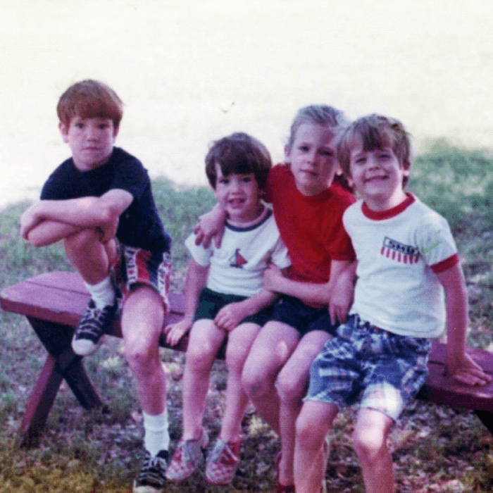 a vintage photograph of 4 kids dressed in red, white and blue