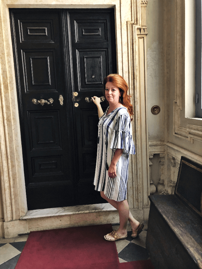 woman with red hair and a blue and white dress standing in front of a tall black door