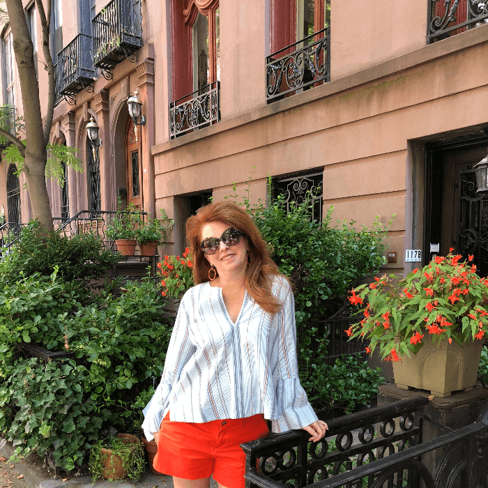 The Curious Cowgirl posing outside a brownstone in NYC