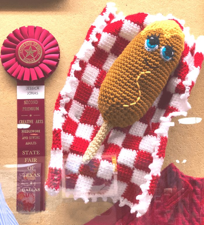 Crochet Corny Dog with a red ribbon prize