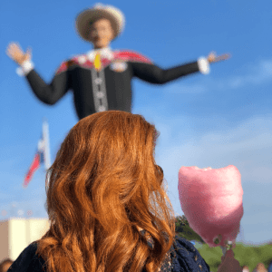Woman with red hair holding a pink cotton candy in front of Big Tex